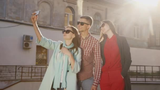 Friends two women and a man doing selfie in the sun. Against the background of an old building