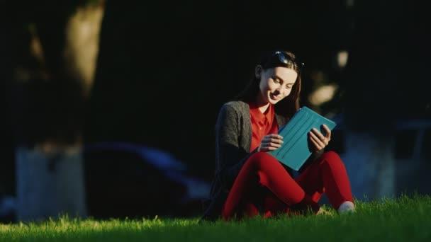 A fiatal nő élvezi a táblát a parkban. Ülve a fűben, arcát megvilágította az esti nap.