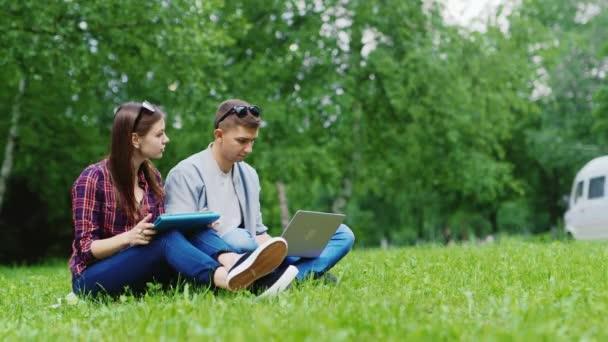 Vysokoškoláků studujících společně v přírodě. Užijte si tabletu a notebook