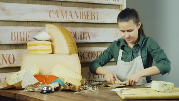 Mladá žena prodávající balíčky kousek sýra na přepážce
