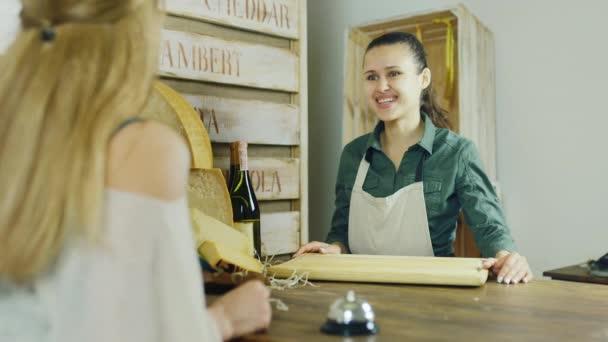 Kupující kupuje kousek sýra, platit za zboží v hotovosti. Kupci z zad, usmívá prodejce