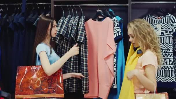 Two friends looking for a new collection of clothes in the store