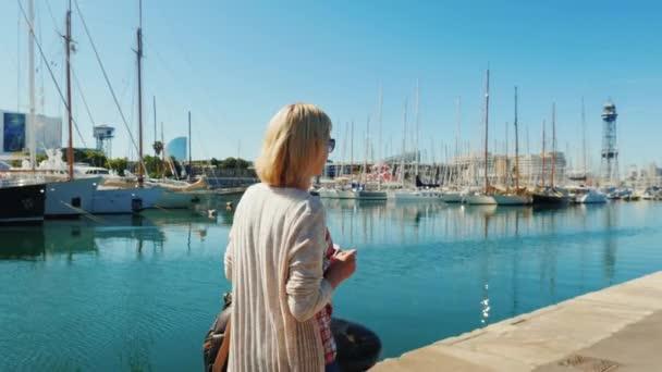 Frau mit Sonnenbrille spaziert mit Yachten am Wasser entlang. Rückansicht, die Bucht von Barcelona