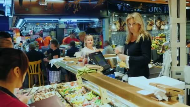 Barcelona, Spain - June 15, 2016: A lively trade in the market, a large crowd of buyers and sellers. The famous la Boqueria market