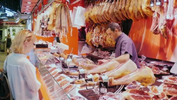 Barcelona, Španělsko - 15 červen 2016: Žena koupí šunka na trhu. Čítač je vyzdoben spoustou vepřové šunky a uzeniny