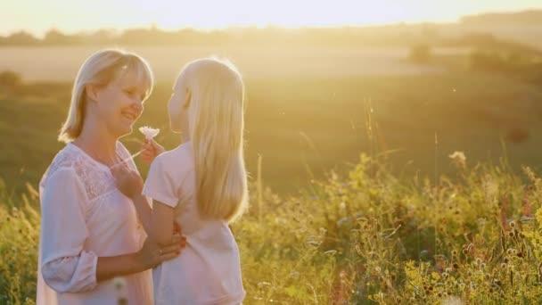 Zärtlichkeit Mutter und Tochter. Mutter spielt bei Sonnenuntergang mit ihrer Tochter