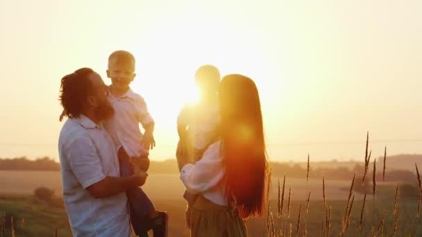 Šťastná rodina hrát s dětmi při západu slunce. Mami, táta a dvě děti