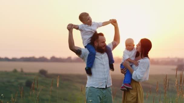 Mladá rodina se dvěma dětmi hraje na přírodu. Na západ slunce