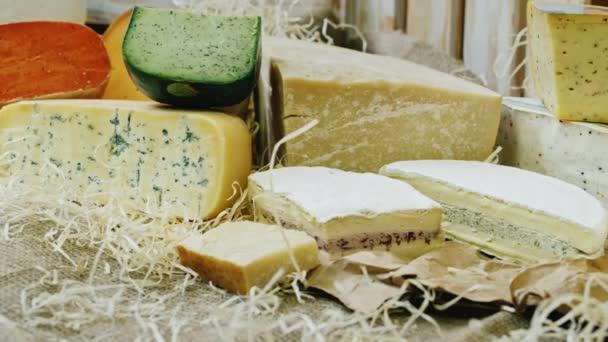 Různých druhů sýra na displeji, ležící na pytloviny a seno