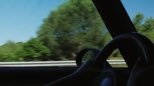 ovladače ruce na volant z jedoucího auta. Auta jedoucí na malebném místě ve Španělsku