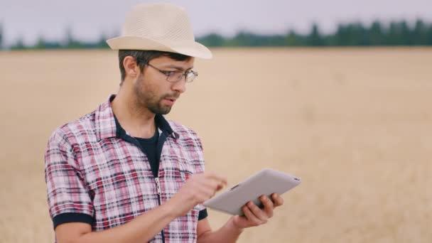 Mladý dobře vypadající farmář s čepici a brýle, pracující na poli. Použití tabletu