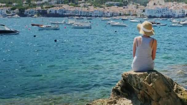 Crane shot: Woman looking at sea, rear view. Spain, Costa Brava