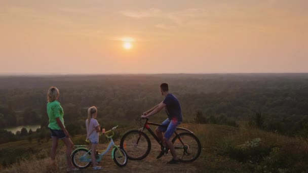 Crane shot: Family together admiring the sunset, standing next to a bicycle