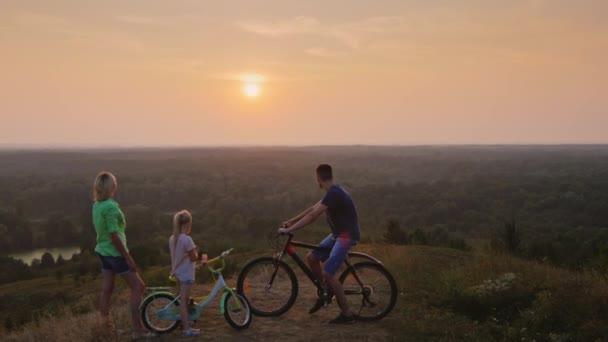 Kranich erschossen: Familie bewundert gemeinsam den Sonnenuntergang, neben einem Fahrrad stehend