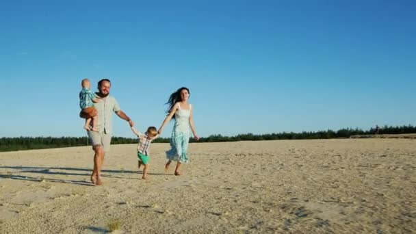 Steadicam shot: Cheerful family running across the sand. Parents and two young sons