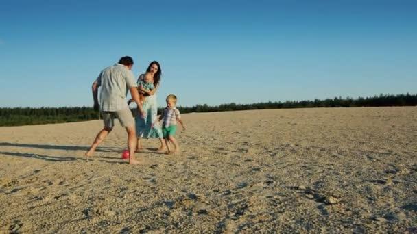 Mladá rodina hraje fotbal s dvěma malými kluky