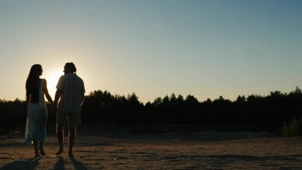 Steadicam výstřel: silueta mladého páru, který jede směrem k zapadajícímu slunci. Pohled zezadu