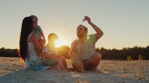 Šťastná rodina s dvěma dětmi - foukat bubliny