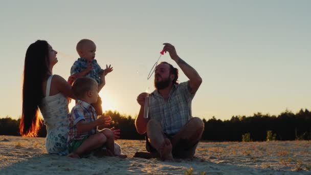 Young family having fun with two kids - blow bubbles at sunset