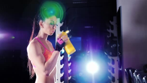 Athletic woman drinking a protein shake in a shaker in the gym. In the rays of spotlights. Sports nutrition