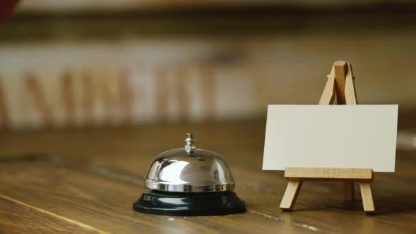 Il visitatore o cliente chiama ping campana. Nelle vicinanze stand con biglietto da visita in bianco per titoli o etichette