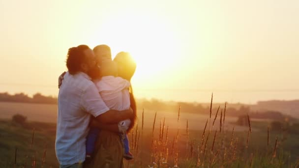 Big family hugging at sunset. Parents and two children