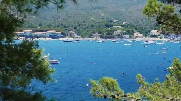 Krásný výhled na moře s jachty a lodě. V popředí stromy. Na skalnatém břehu malé letovisko ve Španělsku