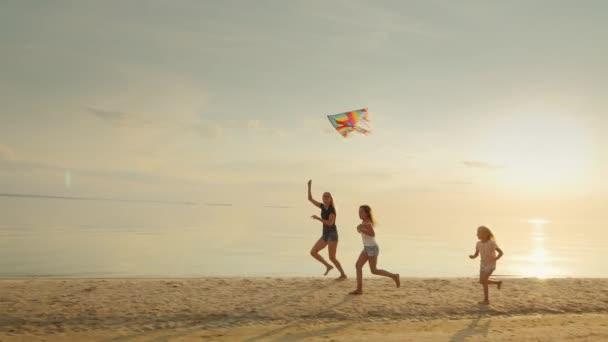 Matka s dvěma dcerami hraje na pláži s drakem. Zábavný běh dohromady. Šťastné dětství