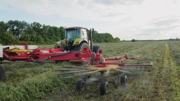 Traktor, pracující v oblasti, sběr v řadě zelené trávy