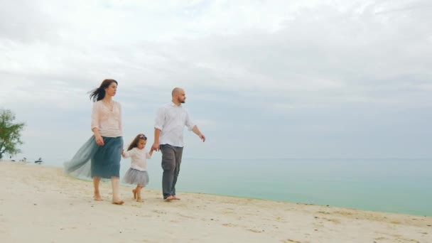 Friendly young family walking along the seashore. A happy childhood, a strong family