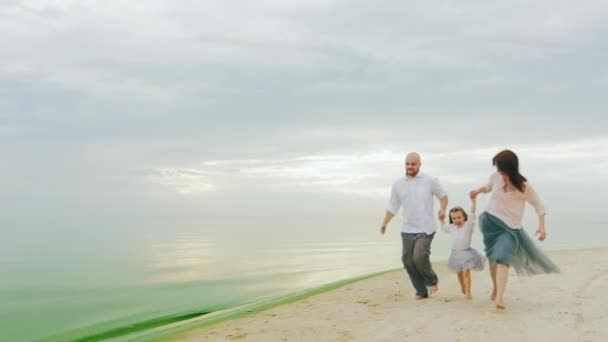 Steadicam slow motion shot: Family fun. Mom dad and daughter run on the beach