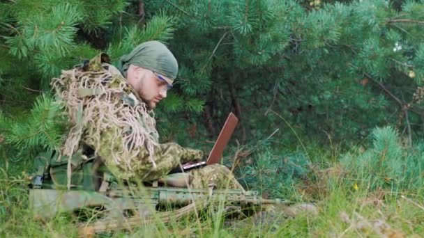 Armed men in camouflage sitting in the woods. It uses laptop. Side view