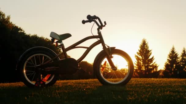 Childrens bicycle standing on a green lawn on the background of the setting sun. Concept - childrens dreams, a happy childhood