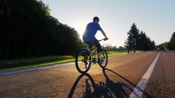 Silueta teenager jde na rovné silnici proti zapadajícímu slunci. Pohled zezadu
