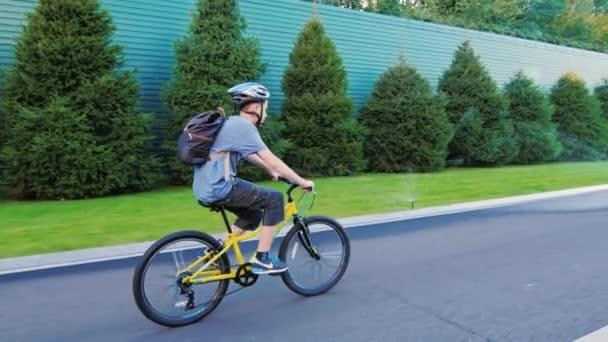 Střela ze steadiamu: v pubertě se jede na kole na asfaltové silnici. Pohled zezadu