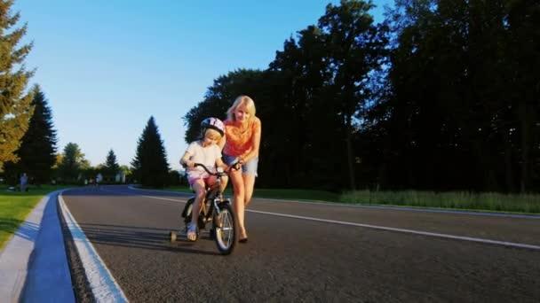 Aktivní hry s dětmi. Žena naučí dívku jezdit na kole, požívá úspěch dítěte