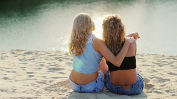 Two friends women sitting on the beach, admiring the beautiful scenery
