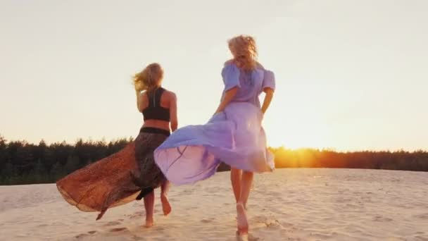 Two women in light dresses run toward the sun. Concept: womens dreams, health, happiness