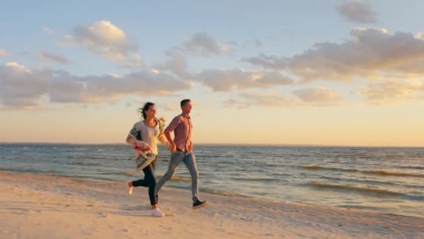 Young couple running along the seashore at sunset. The concept - a happy honeymoon, the energy of youth and health