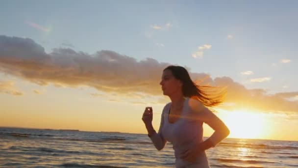 Young sports girl runs with a good figure on the beach. At sunset, beautiful hair fluttering in the wind. Health and healthy lifestyle