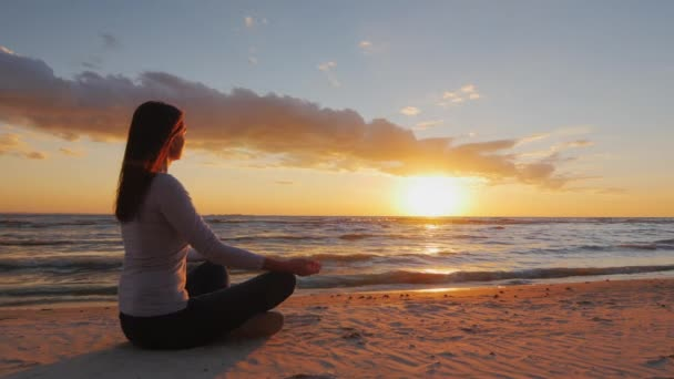 Young woman with long hair sitting on the beach at sunset, meditating. Calm, self-confidence and health