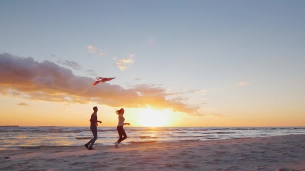 Young couple playing with a kite on the beach at sunset. Steradicam slow motion shot