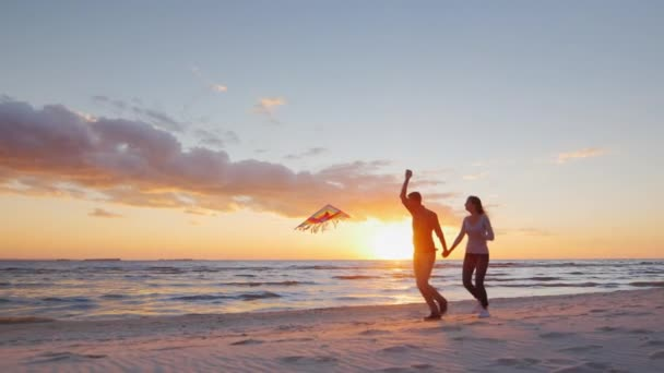Steadicam slow motion shot: Young couple playing with a kite on the beach at sunset