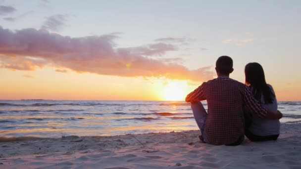 Young romantic couple sitting on the beach, admiring the sunset. Back view