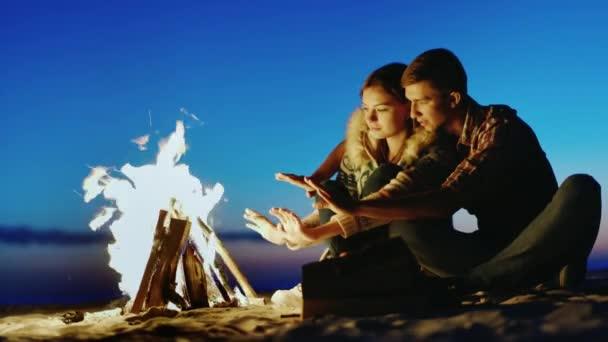 junges Paar, das abends am Feuer sitzt, wärme deine Hände am Feuer