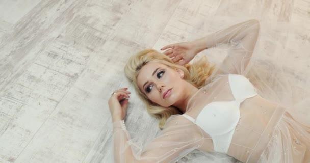Ansicht von oben: Eine junge Frau liegt auf dem Boden und träumt von etwas. In einem schicken weißen Kleid