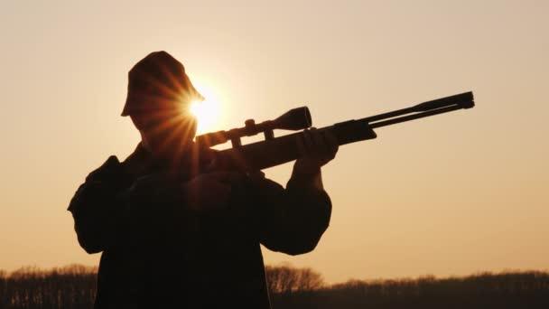 A vadász sziluettje a naplementekor az optikai látvány felé tart.