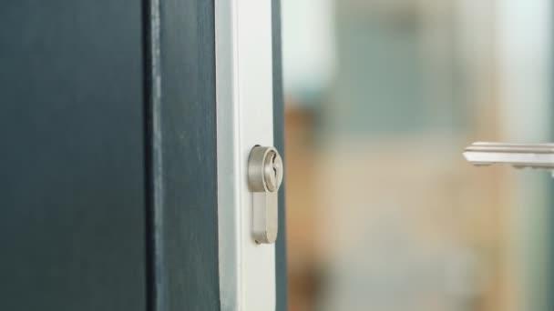 Mann steckt den Schlüssel langsam ins Schlüsselloch der Haustür