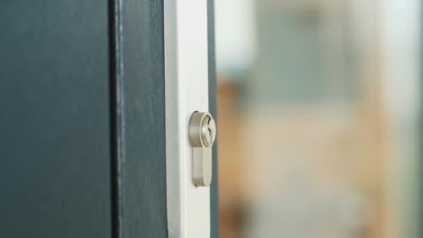 Langsam steckt die Frau den Schlüssel in das Schlüsselloch der Haustür