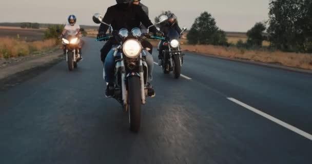 Náklon výstřel: Skupina cyklistů jezdí na dálnici ve večerních hodinách při západu slunce